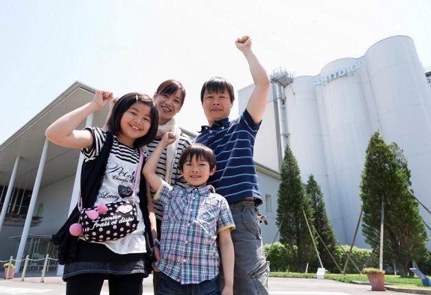 工場前で笑顔でガッツポーズをする親子4人の家族