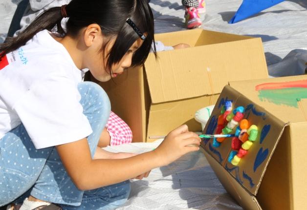 ダンボール制作で色を塗る子どもたち