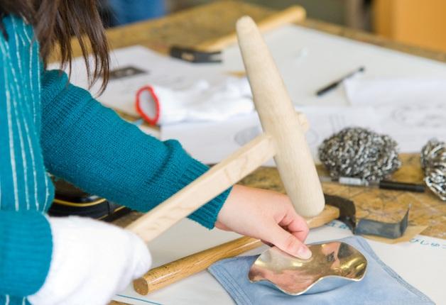 「木槌」と「砂袋」という道具を使って「鍛金」の工程を体験